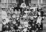 Picture relating to Coorparoo - titled 'Group portrait of matron, sisters and children of the Queen Alexander Home, Coorparoo, Brisbane, Queensland, ca.1917'