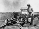 Picture relating to Blackall - titled 'Man standing near a motorised quadricycle, Blackall, Queensland, ca.1919'