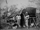 Picture relating to Queensland - titled 'Gold miners outside a bark hut, Queensland, ca. 1870'