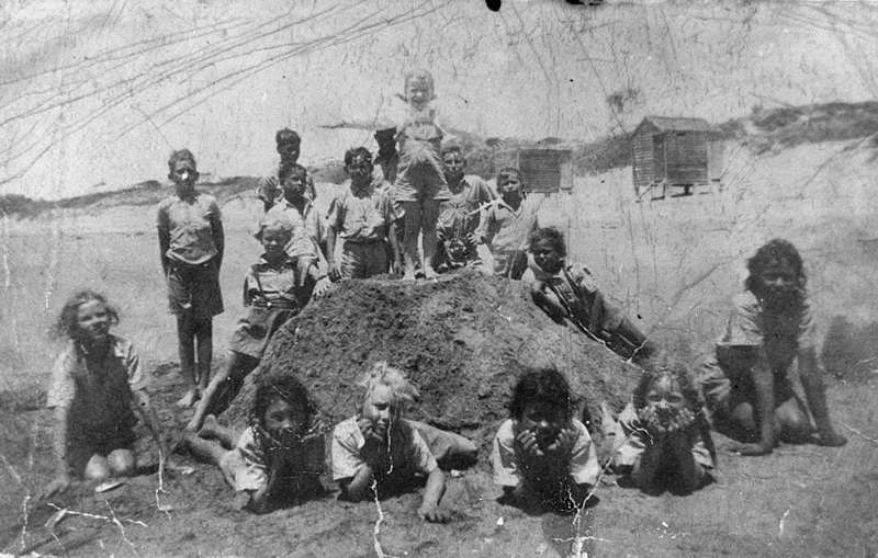 Picture of / about 'Yeppoon' Queensland - Large group of children posed around a mountain of sand, Yeppoon