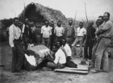 Picture relating to Innisfail - titled 'South Sea Islander labourers gathered around a drum outside a hut in Innisfail, ca.1902'