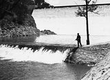 Picture of / about 'Fisher' the Australian Capital Territory - Cotter Dam Wall and stilling pond. Fisherman fly casting into the pond.