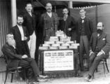 Picture relating to Croydon - titled 'Group of men gathered around a table full of gold ingots from Golden Gate Mine, Croydon, 1904'