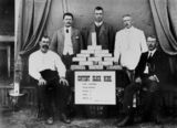 Picture relating to Croydon - titled 'Group of men gathered around a table stacked with gold ingots from the Content Mine, Croydon, 1912'